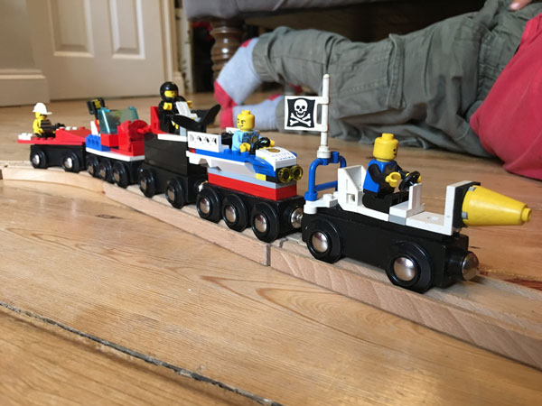 Child playing with Lego wooden trains